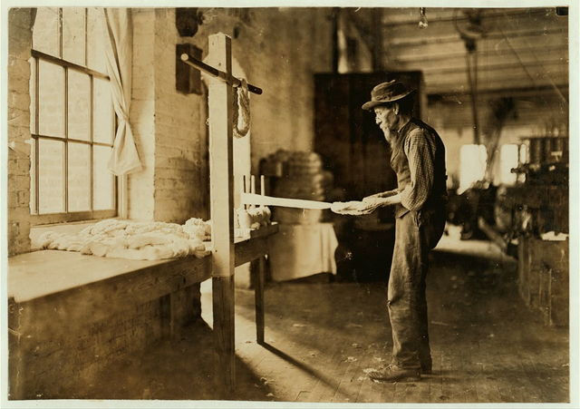 Rhodes Mfg. Company, Lincolnton, N.C. Old man inspecting yarn. Been in cotton mills over 20 years.  Location: Lincolnton, North Carolina.