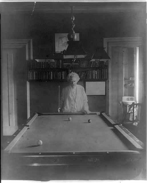[Samuel Clemens, half-length portrait, standing at end of pool table]