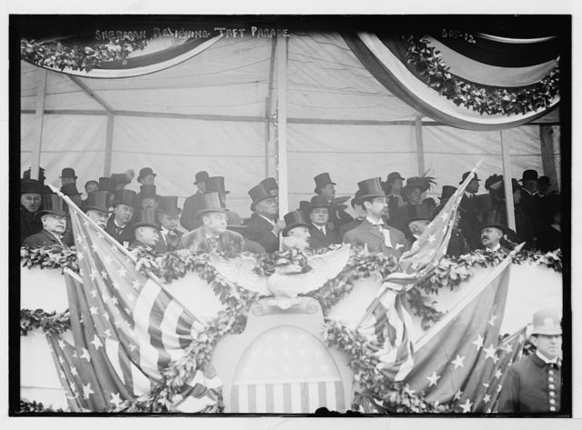 Sherman with others at flag-bedecked podium during Taft Parade, New York