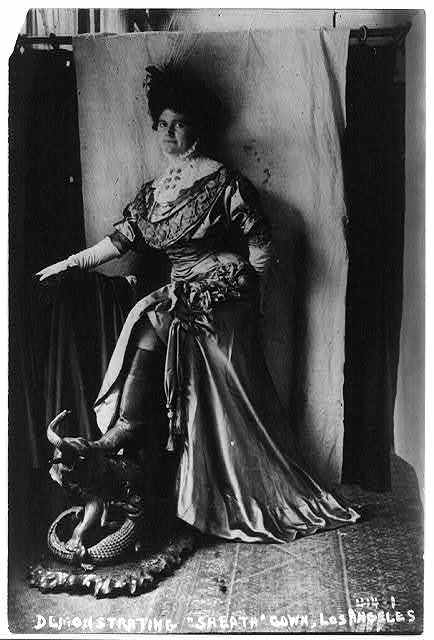 """Shop girl in Los Angeles modeling a so-called """"sheath"""" gown wearing rubber boots to show excess of modesty"""