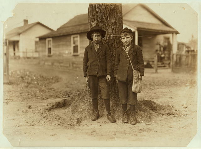 Springstein Mill, Chester, S.C. Malcolm Rogers (Boy with hat) 54 inches high. Be[e]n in mill 3 years. Started at 25 cents and now makes $1.00 a day. Spins part time and doffer part time. Other boy goes to school and helps in mill afternoons and Saturdays. Witness S.R. Hine.  Location: Chester, South Carolina.