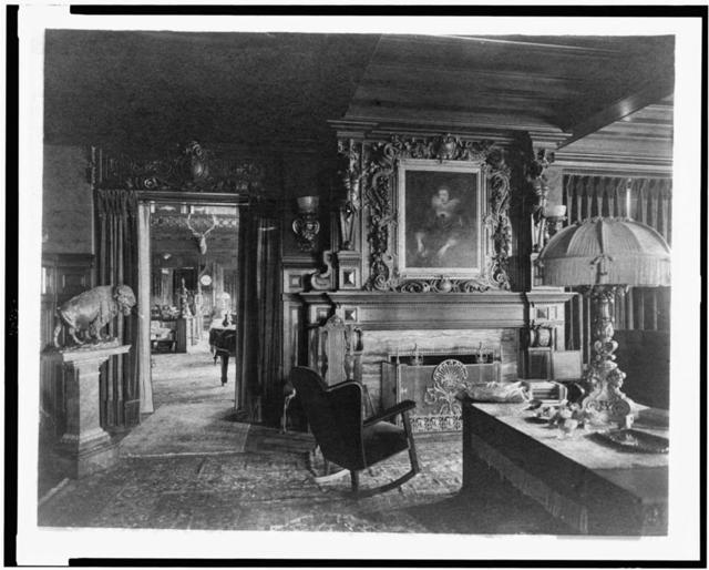 [Study with portrait of woman in Elizabethan dress, over fireplace, fringe lamp at right, and buffalo statue on left; elk head on wall and grandfather clock in background, in home of Edmund Cogswell Converse, Greenwich, Connecticut]