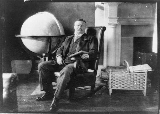 [Theodore Roosevelt, full-length portrait, seated by globe and mantle, facing slightly right, holding book]