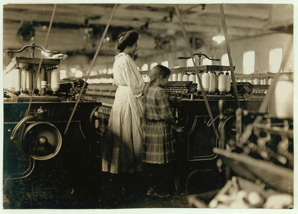 """This was the smallest I could find in the Newton (N.C.) Cotton Mills. Overseer said """"She just brings her sister's dinner,"""" but as it was only 9:30 A.M., and as she worked as faithfully as her sister all the time I was in the mill, I judged she was a regular """"helper."""" She looked to be 8 years old. Others there nearly as small. Location: Newton, North Carolina"""