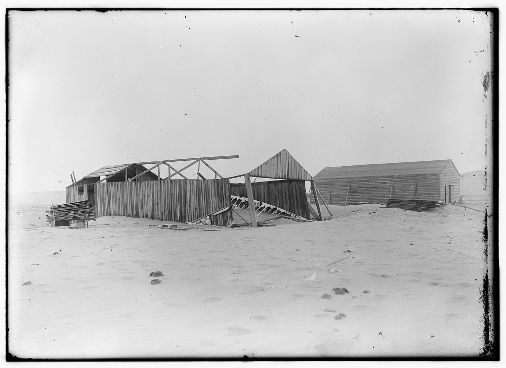 [View of the camp at Kitty Hawk from the northeast, showing its condition at the time of Wilbur's arrival on April 10, 1908. The old 1902 building is on the left, its side walls still standing but its roof and north end gone. The remains of the 1902 glider are on the ground]