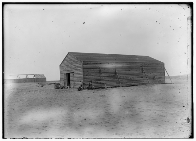 [View of the camp building at Kitty Hawk from the northwest, showing the old building to the left and the newly constructed building on the right, with a window on its east side and outside wall braces visible on its west side]