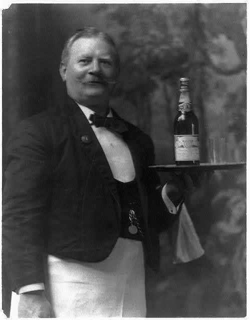 Waiter holding bottle of Budweiser beer on tray