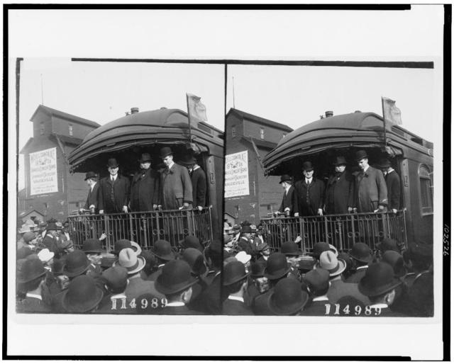 [William Howard Taft, standing on back of railroad car and looking out at crowd, probably during campaign tour]