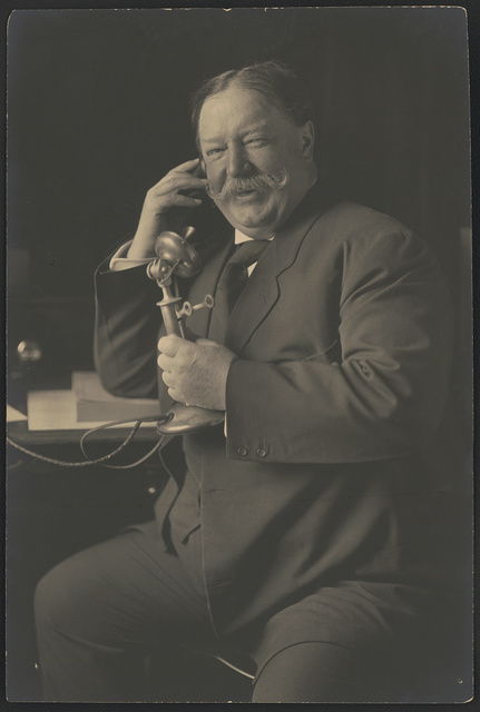 [William Howard Taft, three-quarter-length portrait, seated, facing front, smiling while talking on a telephone as he receives news of his nomination as the 1908 Republican presidential candidate from President Theodore Roosevelt] / Harris & Ewing, Washington, DC.