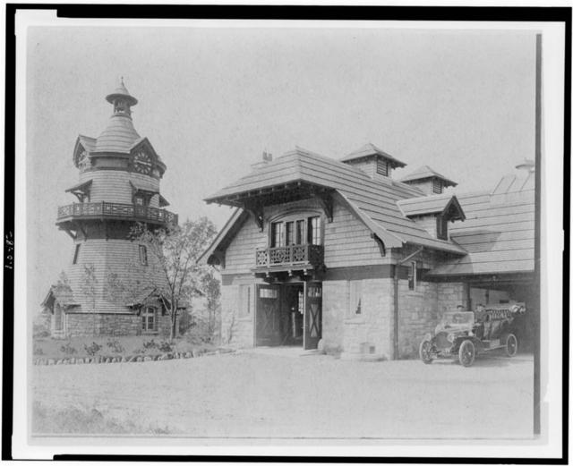 [Windmill-shaped clock tower at left, and part of garage of Edmund Cogswell Converse, with two men on automobile at right, Greenwich, Connecticut]