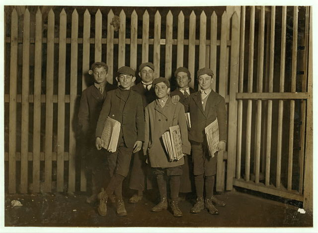 7:00 P.M. Boys selling papers at the depot, Bridgeport, Conn. Smallest one has been selling for 8 years.  Location: Bridgeport, Connecticut.