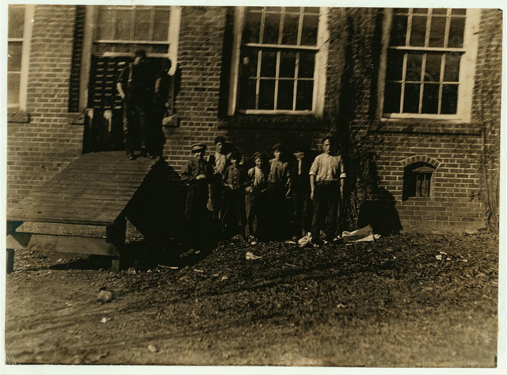 A bad New Years start for the children. A group of doffer boys who were cleaning up in the Atherton Mill, Charlotte, N.C., during the noon hour. The superintendent had forbidden my taking any photos on the company's premises, so I slipped in at noon when authorities were away, gathered the boys together and took this. See photos 472 to 479.  Location: Charlotte, North Carolina / by Lewis W. Hine. Jan 1, 1909.