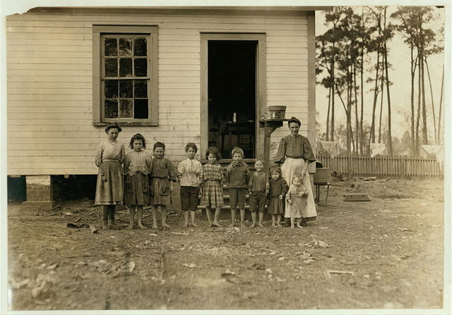 A family working in the Tifton (Ga.) Cotton Mill. Mrs. A.J. young works in mill and at home. Nell (oldest girl) alternates in mill with mother. Mammy (next girl) runs 2 sides. Mary (next) runs 1 1/2 sides. Elic (oldest boy) works regularly. Eddie (next girl) helps in mill, sticks on bobbins. Four smallest children not working yet. The mother said she earns $4.50 a week and all the children earn $4.50 a week. Husband died and left her with 11 children. 2 of them went off and got married. The family left the farm 2 years ago to work in the mill. January 22, 1909.  Location: Tifton, Georgia.