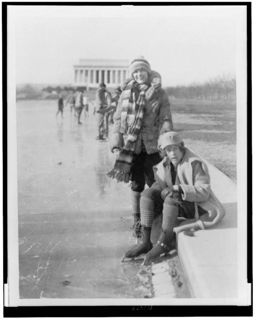 [Abbey Jackson, seated, and Celene DuPuy ice skating on reflecting pool, with Lincoln Memorial in background]