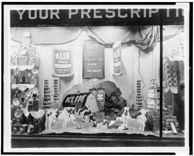 Alarm clocks, powdered milk, and toothpaste in a drug store display window, Washington, D.C.