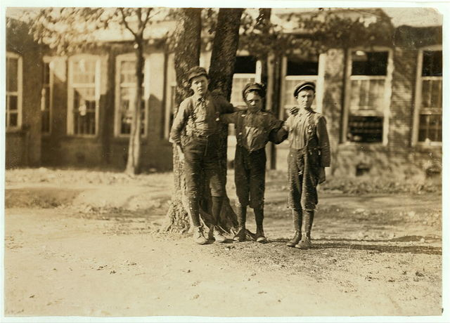 Atherton Mill, Doffer boys Charlotte, N .C. Photo taken during absence of Supt. and contrary to his orders. Tallest boy--Lester Blunt. Been in the mill work 2 years. Middle boy--Eb Saddlefield. Been in mill work 3 years. Boy on the right hand end,--Roscoe Simpson. Been in mill work 3 years.  Location: Charlotte, North Carolina.