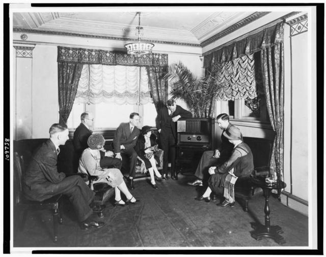 [Atwater Kent, standing by radio, and seven other people listening to the radio, in the Hamilton Hotel, Washington, D.C.]