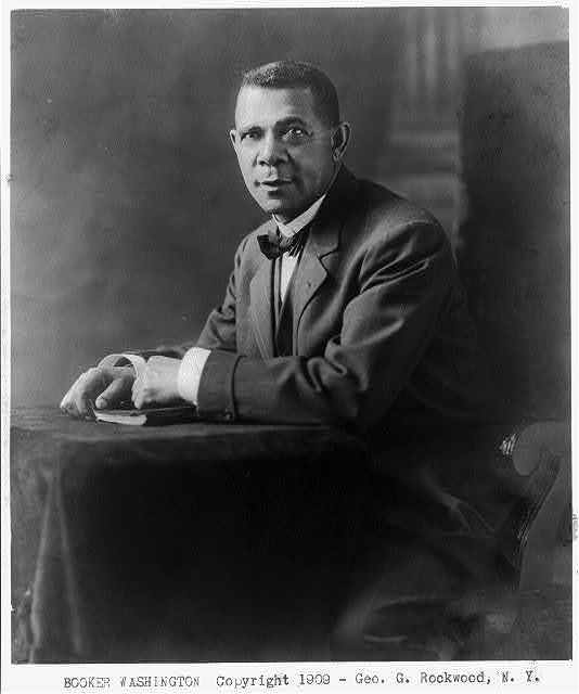 [Booker Taliaferro Washington, 1865-1915, three-quarters length, seated at small table, facing slightly left]