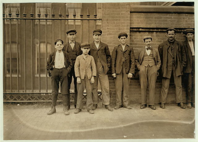 Boy on left hand end (hands in pockets) is Peter Carlos, 33 Waldron St. Been working in Mill No. 1 for 1 1/2 years. Smallest boy is Nicholas Karambles, 33 Waldron Street. Cocheco Mfg. Co., Dover N.H. 6 A.M., May 15, 1909. I counted 23 boys and girls that looked to be under 14 years of age going into these mills one morning, and could not watch all the gates.  Location: Dover, New Hampshire.