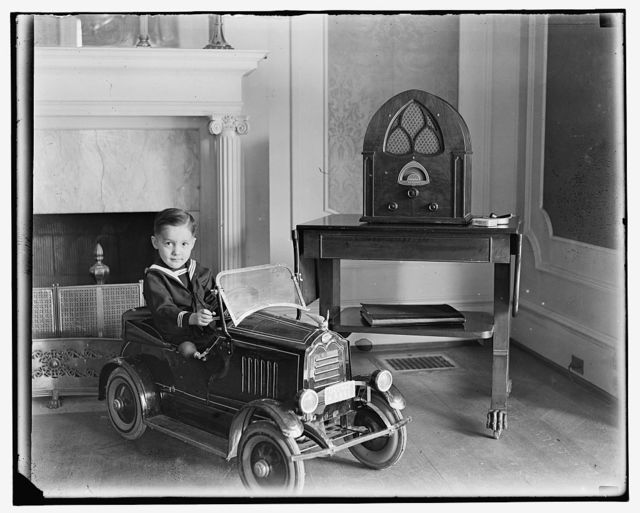 [Child seated in toy automobile]