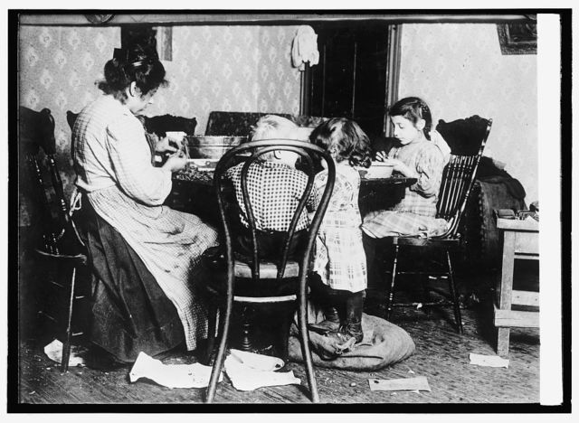 Children 4-6-9, picking nuts in a basement tenement; filth abounds and room is dark & damp.
