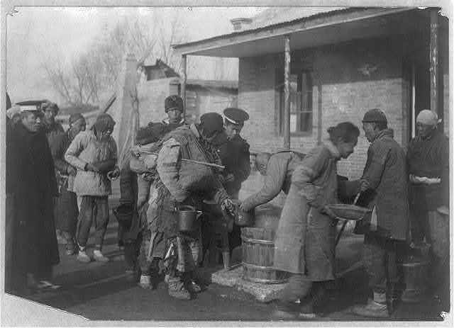 Chinese soldiers supervising distribution of famine relief rations