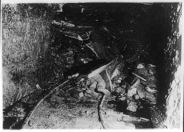 [Dead (?) coal miner under rock after cave-in in tunnel]