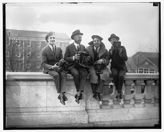 [Four unidentified photographers with cameras]