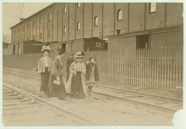 """Group coming out of Great Falls Mfg. Co., Somersworth, N.H., 6 p.m. May 18, 1909. See photos and labels #[not filled in]. Many of these young boys and girls go in as """"helpers"""" to mothers, fathers, brothers and sisters, but they work regularly.  Location: Somersworth, New Hampshire."""