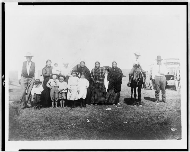 [Group of Kickapoo Indians, standing outside tent, dressed in Euro-American clothing]
