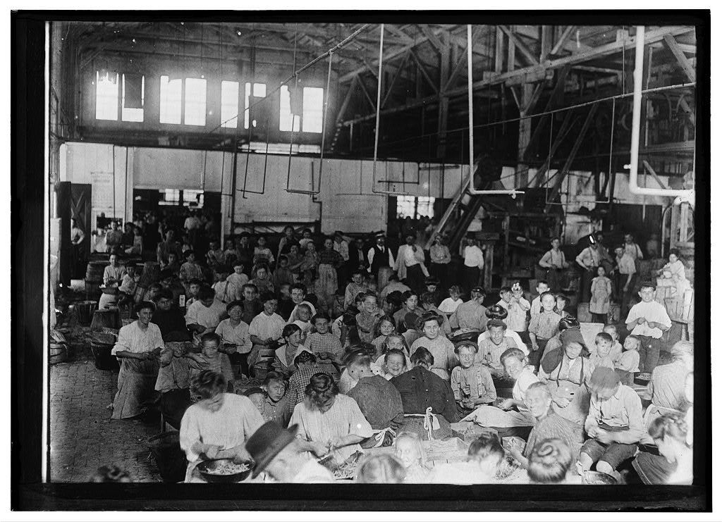 Group, showing a few of the workers stringing beans in the J. S. Farrand Packing Co. Baltimore, Md. Those too small to work are held on laps of workers or stowed away in boxes.  Location: Baltimore, Maryland.
