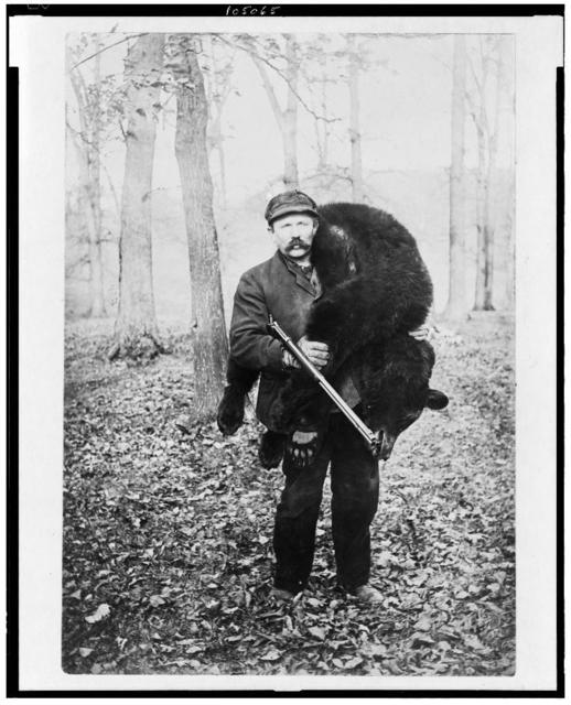 [Hunter carrying a large bear]