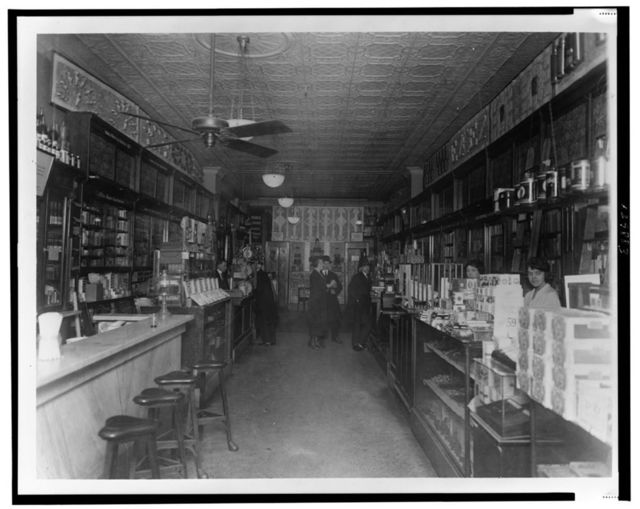 [Interior of People's Drug Store, 11th and G Streets, Washington, D.C., with employees behind the counters and customers]