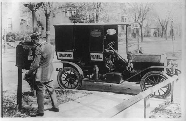 """[Mailman emptying mailbox, automobile marked """"United Mail"""" at curb]"""