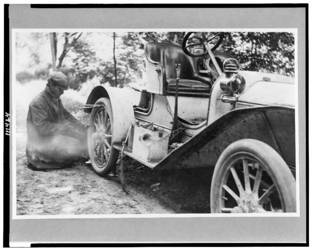 [Man fixing tire on a Buick roadster outside of Liberty, on a trip through upstate New York]