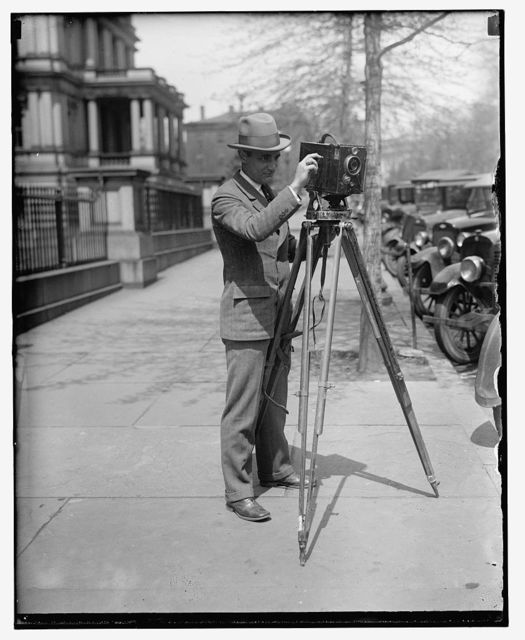 "[Man using a motion picture camera on a tripod, possibly a Debrie or Parvo ""L"" camera]"