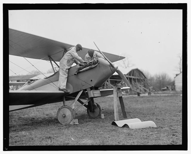 [Men examining airplane engine]