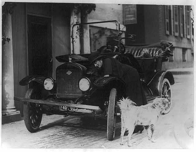 [Miss Maude Younger of San Francisco, Legislative Secty. of the National Womans Party, who has arrived in Washington to attend the Convention of the Womans Party, working on her Ford car - her dog, Sandy, is in the foreground]
