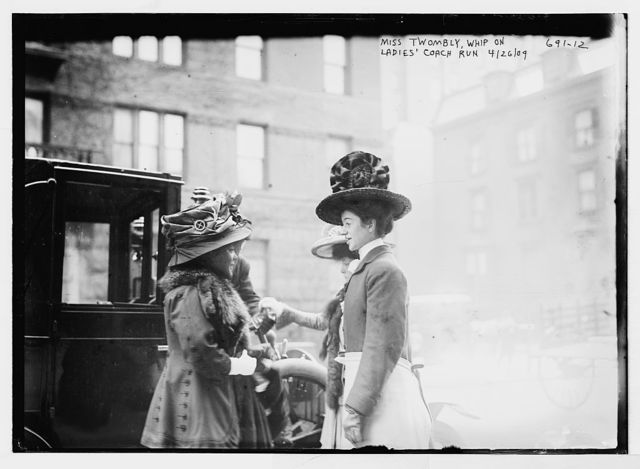 Miss Twombly, whip of Ladies Coach Run, and two other ladies beside coach on street, New York