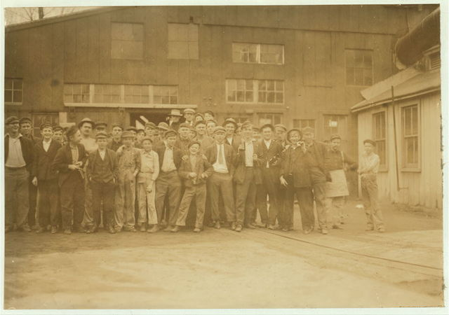 Noon-hour. Cumberland Glass Works, Brigeton[sic], N.J. Smallest boy in middle of front row and one on right-hand end have been in this pant four years. See also photos #957 to 971.  Location: Bridgeton, New Jersey.