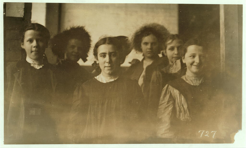 Noon hour, May 5, 1909, in the drawing-in room of American Woolen Co., Winooski, Vt. In front row are:- Right hand end, Allexina Lavelley; next - Anna Cross; next - Cecile Cauchon. In back row, right-hand, Lena Campbell; next, Albina Seymour. I counted 20 girls (under 14) going in at 7 a.m.  Location: Winooski, Vermont / Photo by Lewis W. Hine.