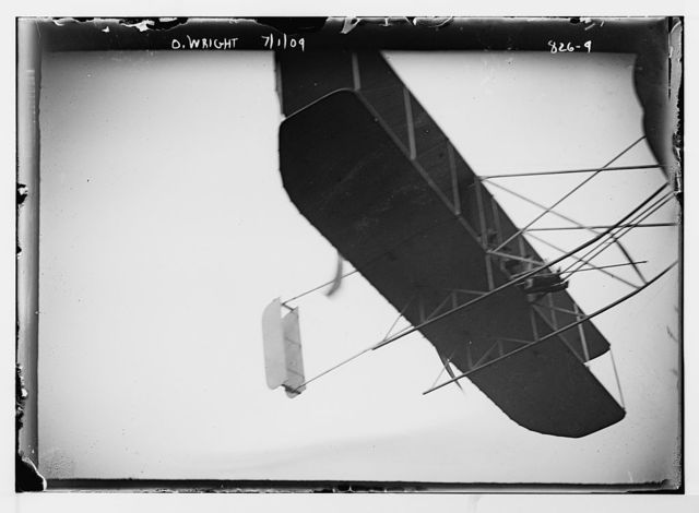 O. Wright and aeroplane, in flight