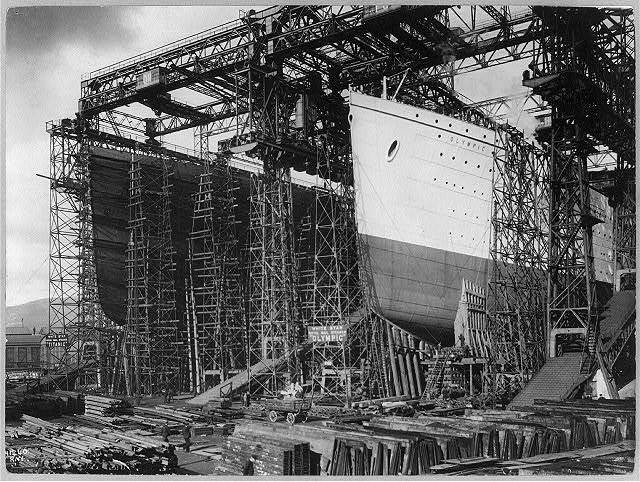 OLYMPIC and TITANIC - view of bows [in shipyard construction scaffolding]