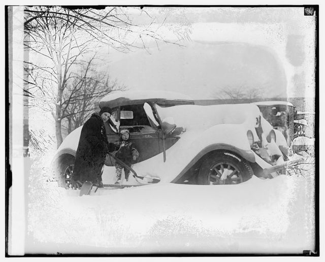 [Person clearing automobile covered in snow]