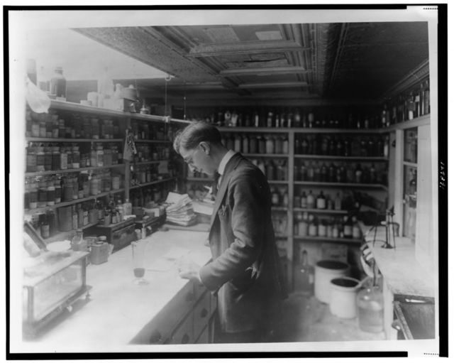 [Pharmacist at People's Drug Store, No. 5, 8th and H Streets, N.E., Washington, D.C., looking at prescriptions(?) on the counter in room lined with shelves of pharmacy bottles]