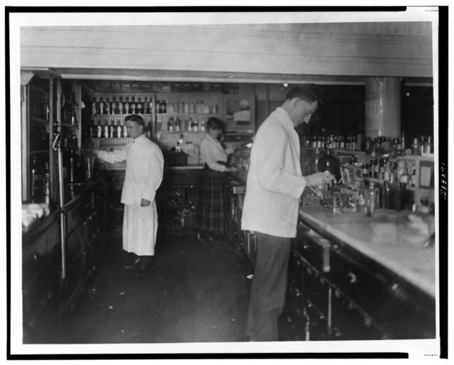 [Pharmacists at People's Drug Store, 7th and E Streets, N.E., Washington, D.C., at counter preparing medications]