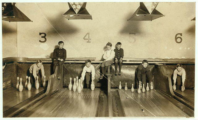 Photo of boys working in Arcade Bowling Alley, Trenton, N.J. Photo taken late at night. The boys work until midnight and later. I found practically no small boys selling late in the evening and several persons said it was not done except in baseball season.  Location: Trenton, New Jersey / Photo by Lewis W. Hine., Dec. 20, 1909.