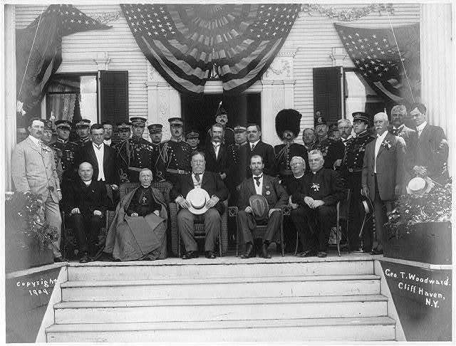 President Taft, Governor [Charles] Hughes, Cardinal Gibbons and other state and church dignitaries [posed outside at top of steps] at the Catholic Summer School of America, Cliff Haven, N.Y.