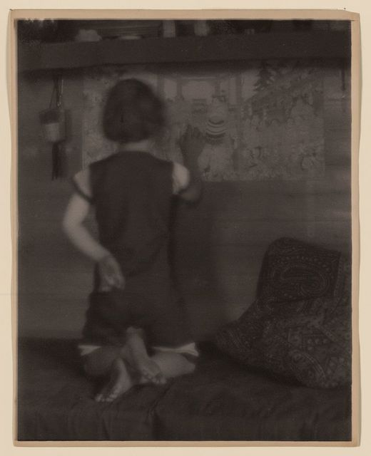 [Ruth Ruyl in shorts on divan, back to camera, examining Japanese prints on wall]