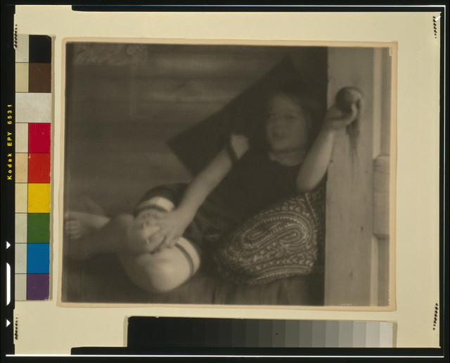[Ruth Ruyl in shorts on divan (sofa w/out back), reclining, holding doorknob of open door]